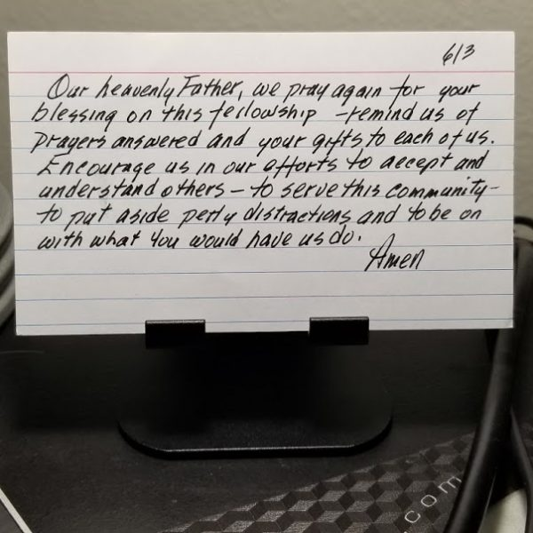 index card on phone stand at desk